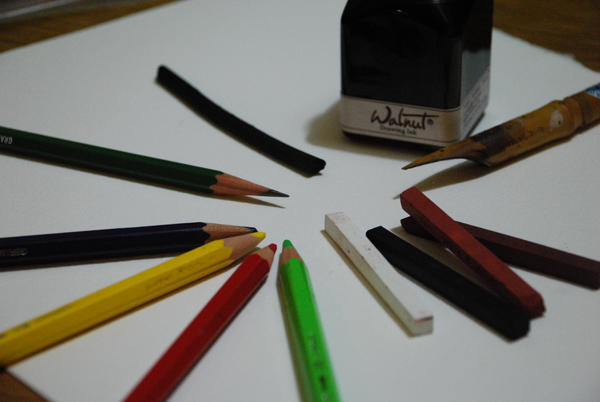 A bottle of walnut ink and a bamboo pen, four colors of Conté crayons (bistre, sanguine, black, and white), four colors of colored pencils, a graphite pencil, and a piece of vine charcoal.