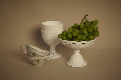 The grapes establish dominance in an otherwise bland still life painting setup.