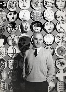 Fornasetti in front of a wall filled with his plates.