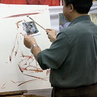 Artist Jove Wang uses a source photo to transfer his composition to canvas.