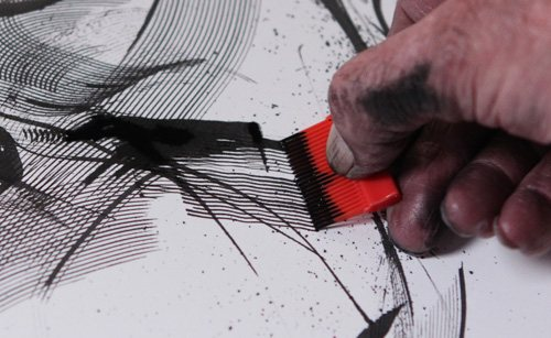 Marshall Arisman using a comb to create marks on his drawing surface.