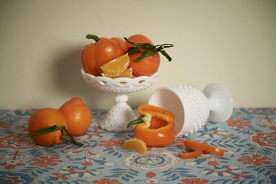 A still life composition against a patterned background can work well together if colors correspond, but objects don't come as sharply into focus as they might against a neutral surface.