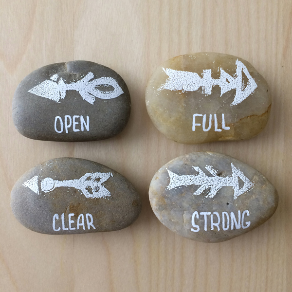 Make magnets. These, too, can be super simple. I carved some stamps and embossed the symbols on the rocks using white embossing powder, then wrote my power words with a white paint pen.
