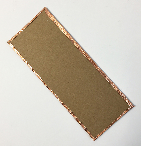 Metal embossing attached to chipboard
