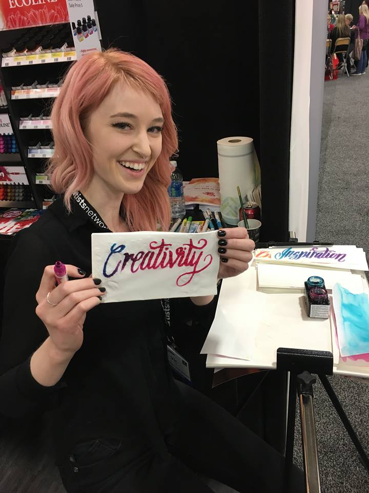 Artist Vic Hollins calligraphies one of her favorite words for the napkin doodle challenge at Art Materials World.