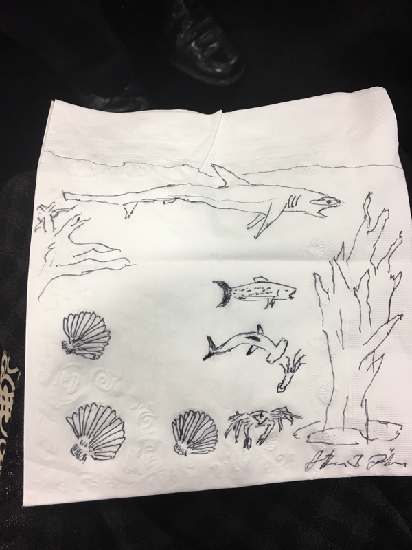 Stefan Lohrer dropped off his first napkin doodle with the wrong person and couldn't bear to take it back so he made us a second edition. He took his theme from the seashell embossing on the napkin, creating a seascape with a trio of sharks.
