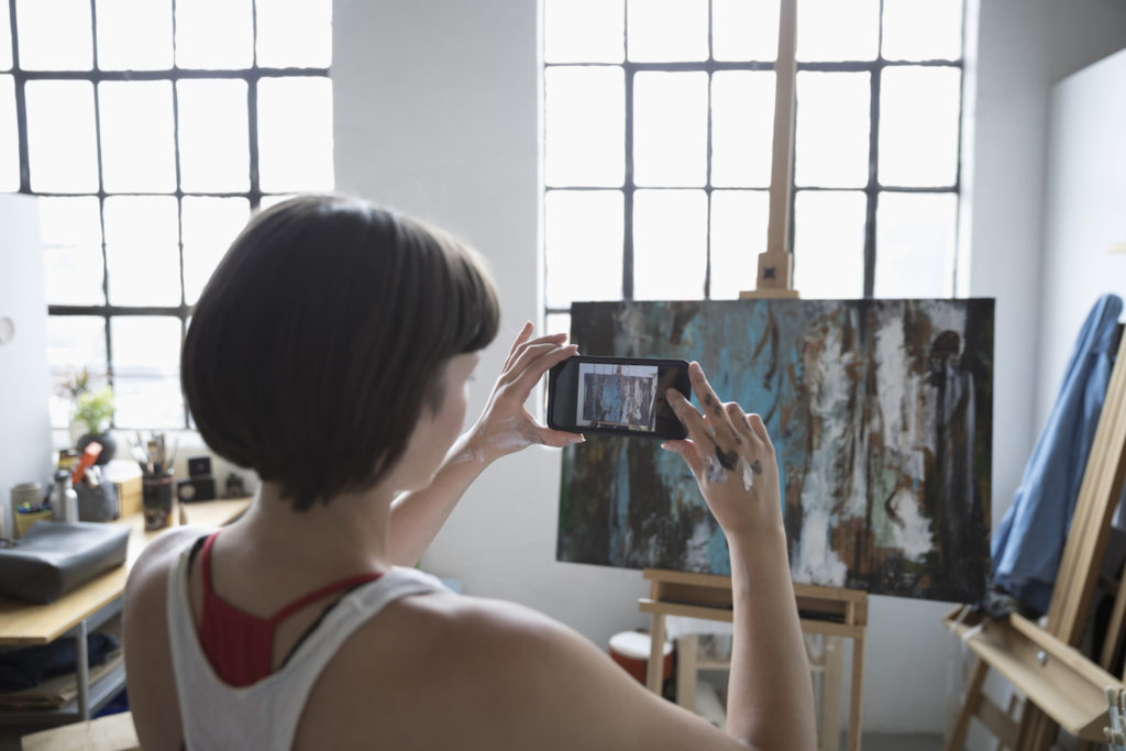 Artist taking picture of painting, photo courtesy of Getty Images | how to sell art online -- article by Artists Network