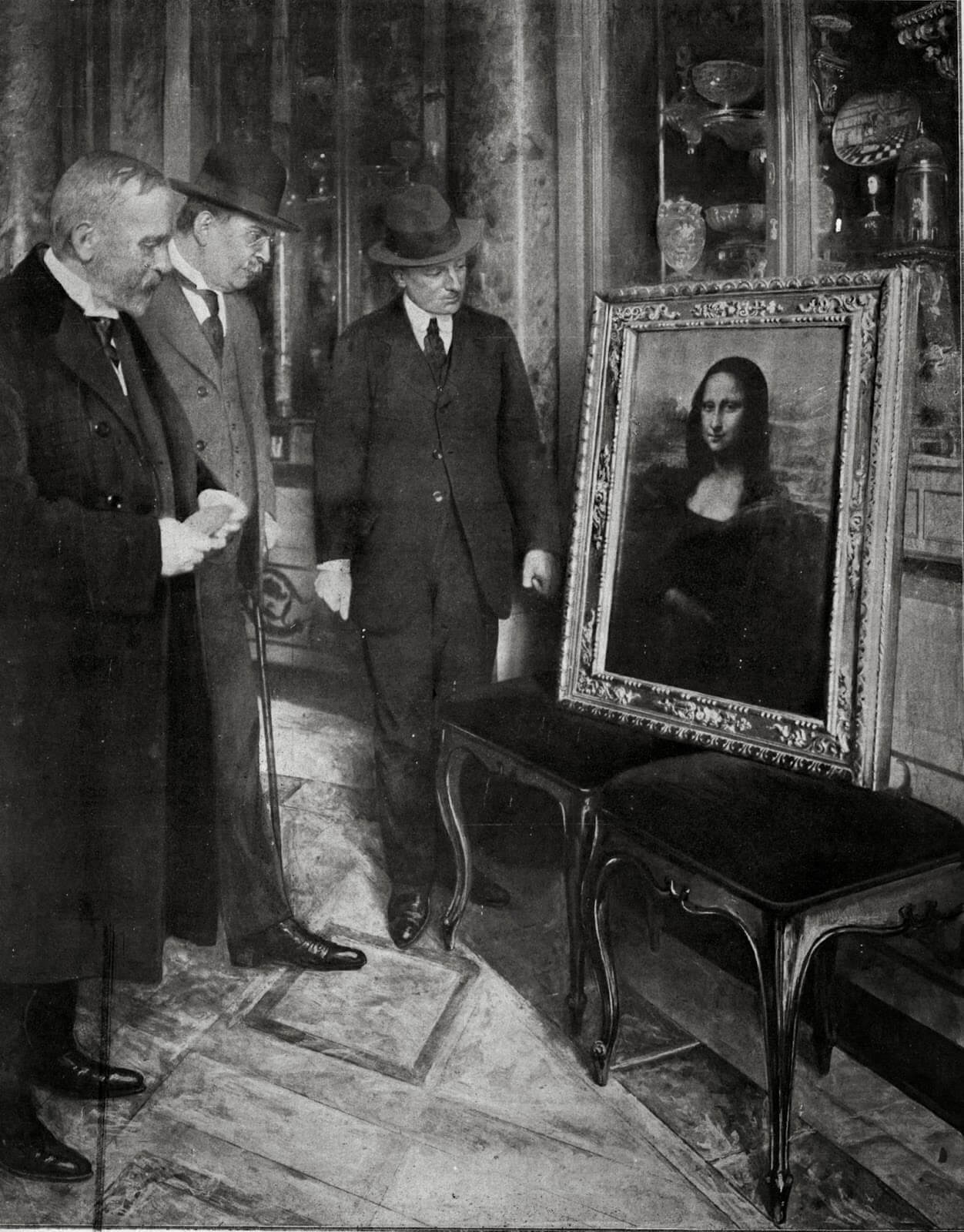 The Mona Lisa on display in the Uffizi Gallery, in Florence, 1913. Museum director Giovanni Poggi (right) inspects the painting.