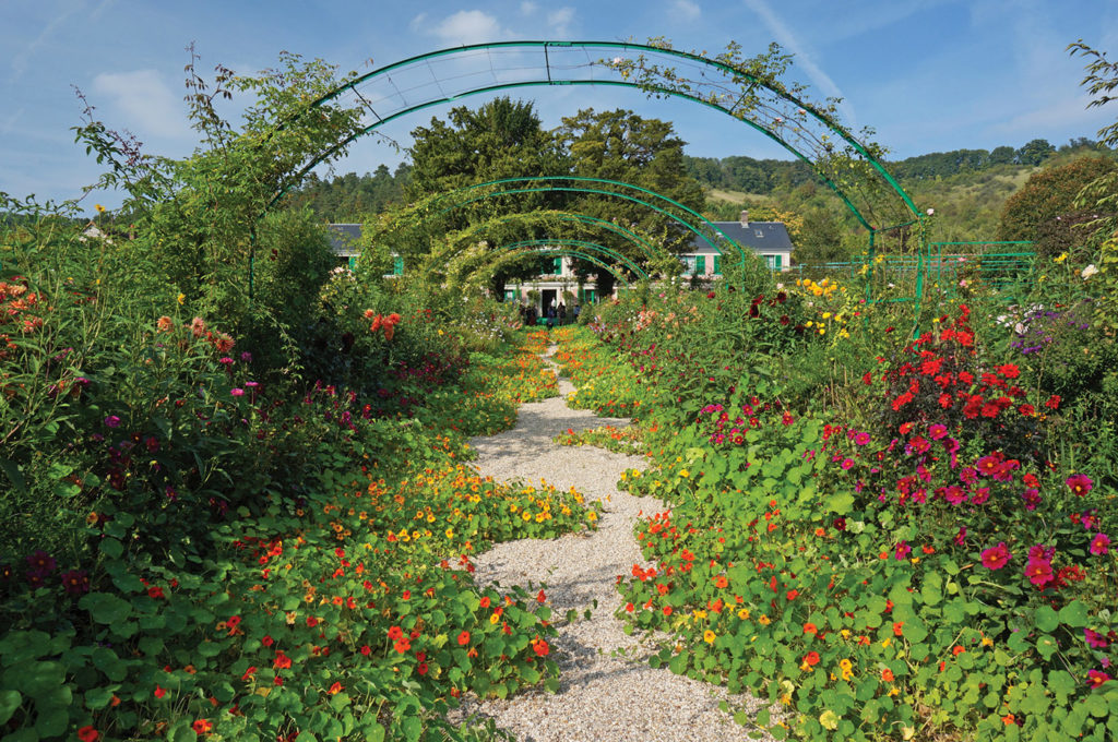Summer gardens framed by archway with Claude Monet's home in the background in Giverny, France.