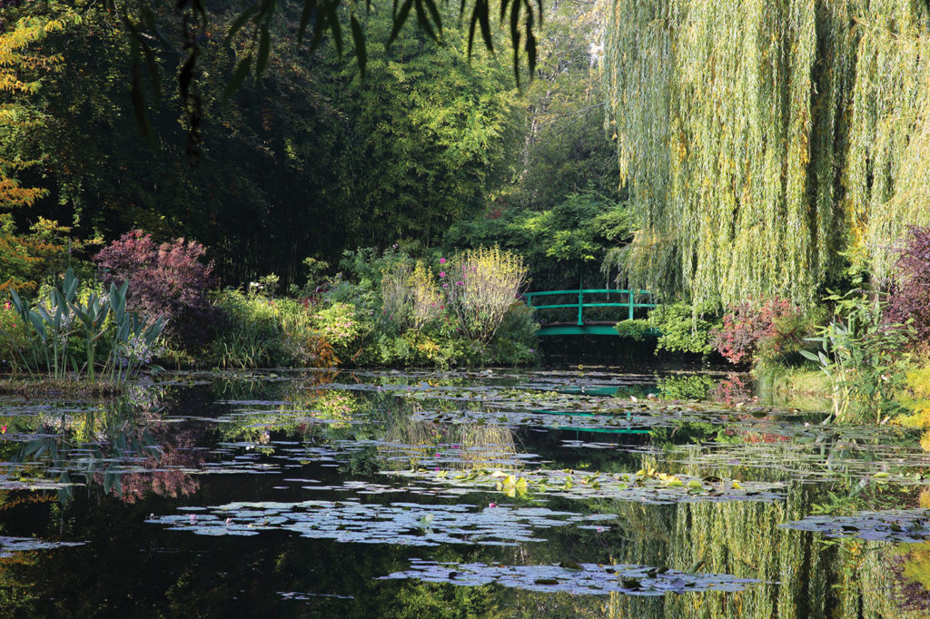 Water lily pond with Japanese bridge in autumn, Monet's Garden, Giverny, France.
