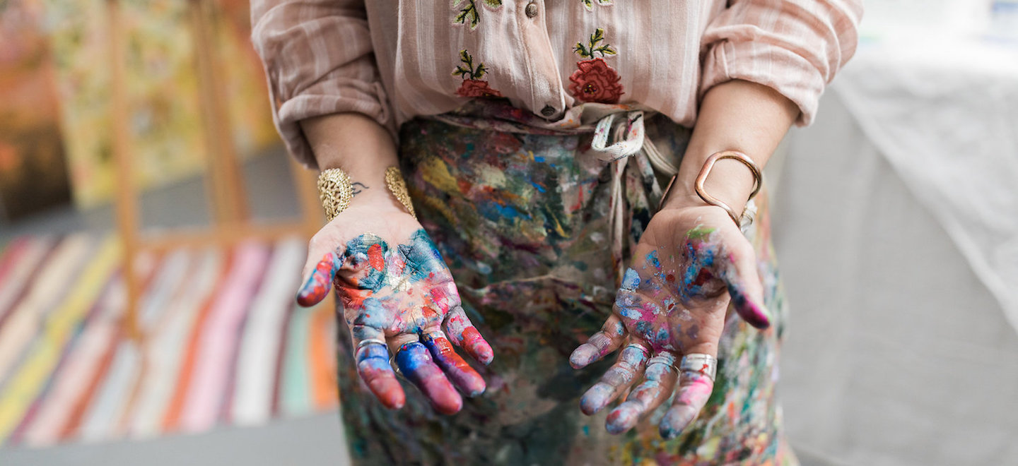 Carrie Schmitt with paint on her hands -- how daily creative acts can empower your life and art | article by Artists Network