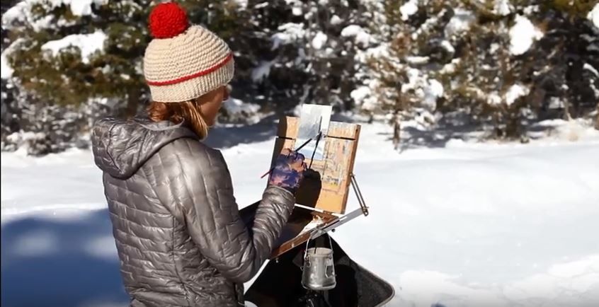 Emilie Lee painting snowy pine trees near Butte, Montana.