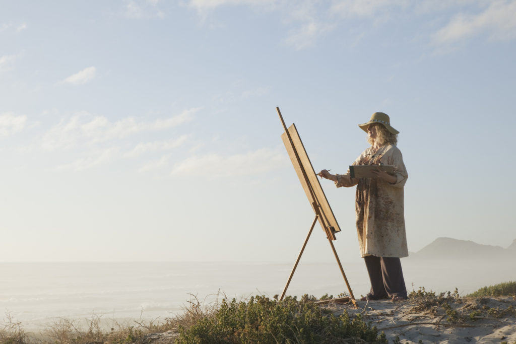 Photo of female painter outdoors, courtesy of Getty Images | Why Artist Retreats Are So Important | Artists Network