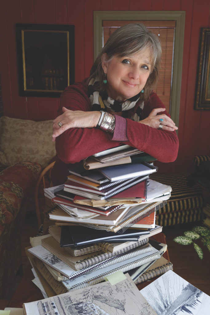 Photo of Liz Haywood-Sullivan with a pile of sketchbooks, courtesy of Michael Sullivan | Why Having an Artist Sketchbook is Key to Better Art | Artists Network