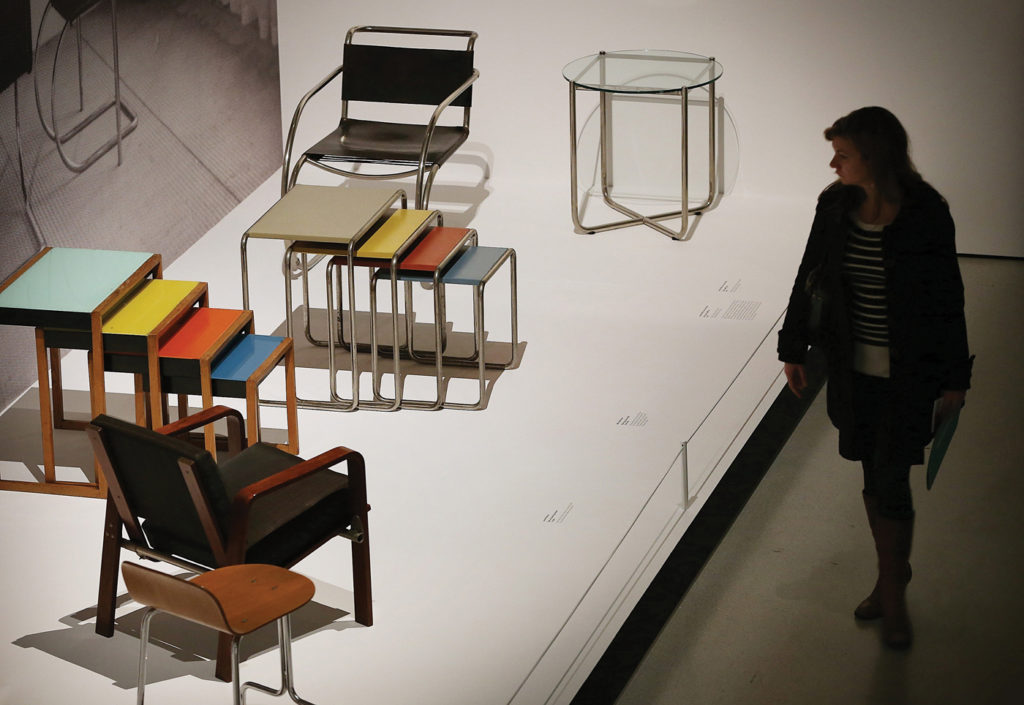 """A visitor looks at tables and chairs on display at the 2012 """"Bauhaus Art as Life"""" exhibition, held at the Barbican, in London. Peter MacDiarmid/Getty Images"""