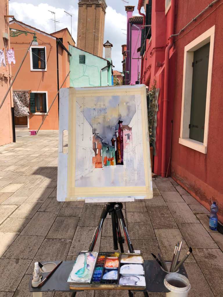 Thomas's easel set up in a colorful street on the Italian island of Burano.